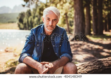 Portrait of mature man sitting near a lake staring at camera. Senior caucasian man relaxing on a log by the lake on a summer day. - stock photo