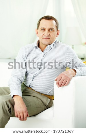 Portrait of mature man sitting on sofa and looking at camera - stock photo