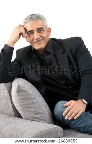 Portrait of mature man sitting on sofa, smiling, isolated on white background.