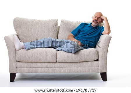 Portrait of mature man sleeping  on the couch isolated on white - stock photo