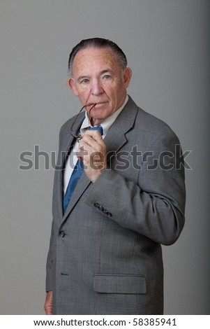 Portrait of mature man standing wearing gray coat and holding his glasses in hand. - stock photo