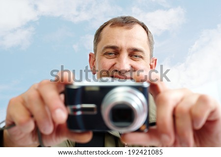 Portrait of mature man taking pictures against cloudy sky - stock photo
