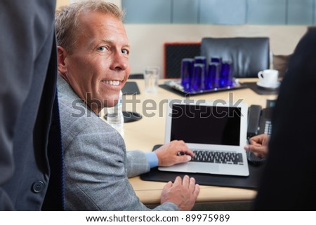 Portrait of mature man using laptop in office - stock photo