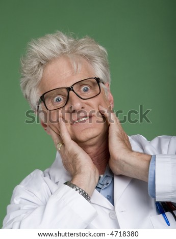 Portrait of mature man wearing white lab coat & glasses with bug-eyed expression. - stock photo