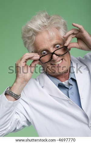 portrait of mature man wearing white lab coat with bug-eyed expression. - stock photo