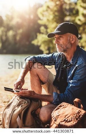 Portrait of mature man with a compass sitting with backpack looking away at a view. Senior hiker sitting by a lake on summer day. - stock photo
