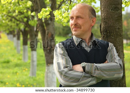 portrait of mature  man with crossed hands outdoor - stock photo