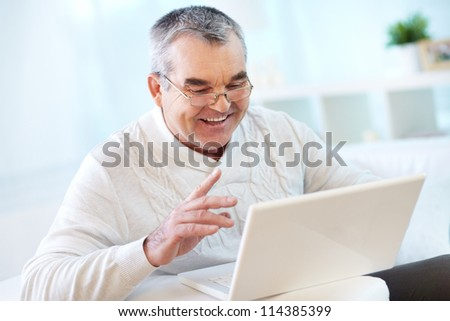 Portrait of mature man working with laptop at home - stock photo