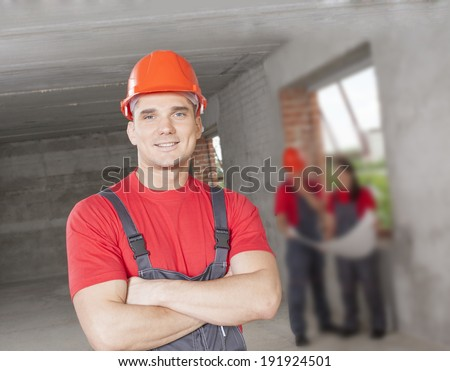Portrait of mature manual worker in uniform holding a project three colleagues near window in gray concrete wall background  - stock photo