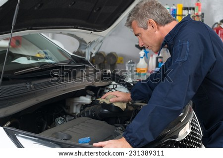 Portrait Of Mature Mechanic Looking At Car Engine In Garage - stock photo