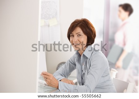 Portrait of mature office worker smiling at camera, holding document, colleague in background.