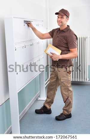 Portrait Of Mature Postman Putting Letters In Mailbox - stock photo