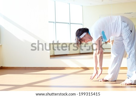 Portrait of mature sporty female doing physical exercise in sport gym  - stock photo