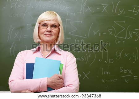 Portrait of mature teacher with copybooks looking at camera with blackboard on background