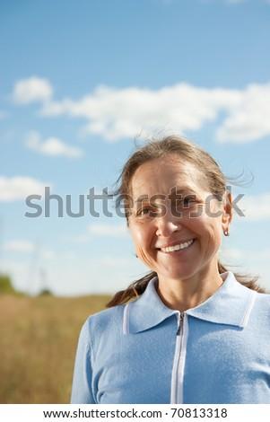 Portrait of mature woman against summer landscape - stock photo