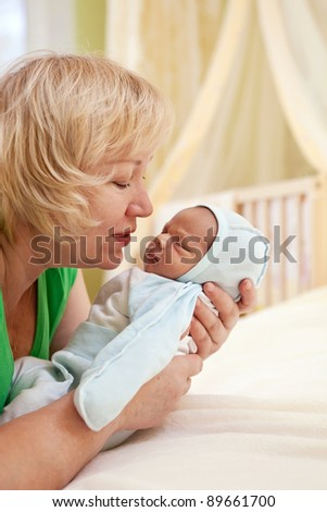 Portrait of mature woman and her newborn grandson - stock photo