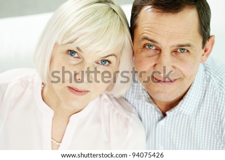 Portrait of mature woman and man looking at camera