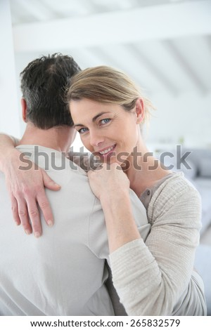 Portrait of mature woman embracing her husband - stock photo