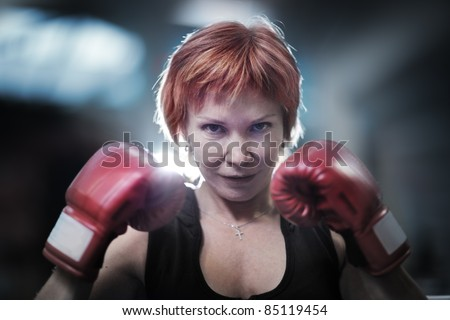 Portrait of mature woman in boxing gloves looking at camera. Closeup. - stock photo