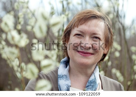 portrait of mature woman in spring pussywillow plant - stock photo