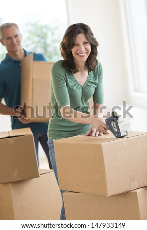 Portrait of mature woman packing cardboard box with man standing in background at home