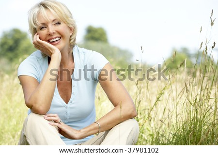 Portrait of mature woman sitting in countryside - stock photo