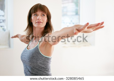 Portrait of mature woman stretching her arms and looking away at gym. Beautiful woman performing yoga in warrior pose, Virabhadrasana. - stock photo