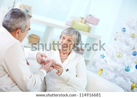 Portrait of mature woman taking small giftbox from her husband - stock photo