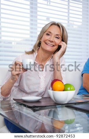 Portrait of mature woman talking on cell phone while having a cup of tea - stock photo