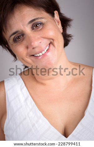 Portrait of mature woman wearing white outfit on grey background