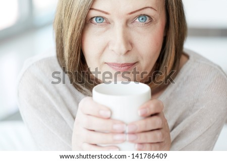 Portrait of mature woman with cup looking at camera - stock photo