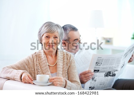 Portrait of mature woman with cup of tea looking at camera on background of her husband reading newspaper - stock photo