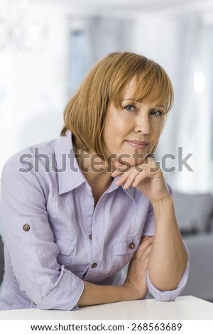 Portrait of mature woman with hand on chin sitting at table in house - stock photo