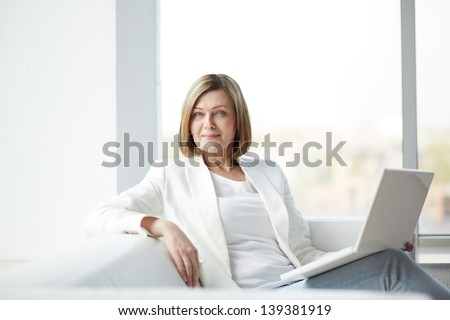 Portrait of mature woman with laptop looking at camera - stock photo