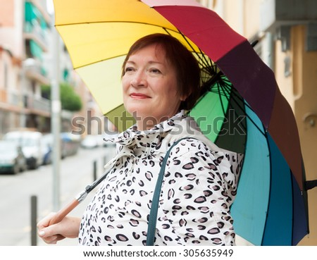 portrait of mature woman with umbrella in autumn   - stock photo