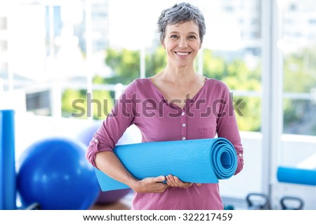 Portrait of mature woman with yoga mat while standing in fitness studio - stock photo