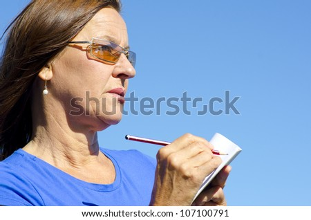Portrait of mature woman writing notes on paper with pen, isolated with blue sky as background and copy space. - stock photo