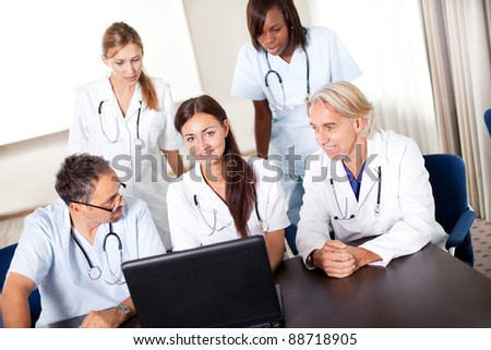 Portrait of mature young doctors working together looking at laptop in a meeting room - stock photo