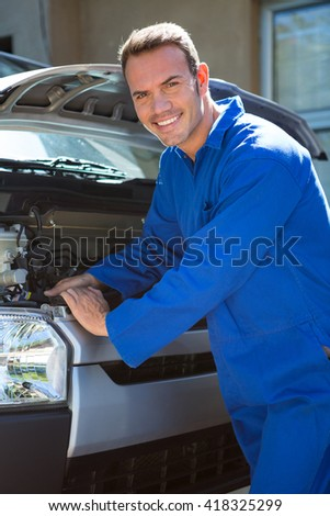 Portrait of mechanic examining the car at the repair garage
