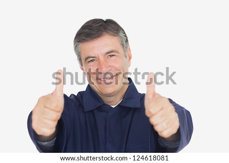 Portrait of mechanic gesturing thumbs up against white background