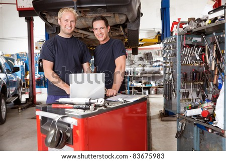 Portrait of mechanics with laptop in auto repair shop - stock photo