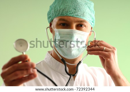 Portrait of medical assistant in cap and mask using stethoscope