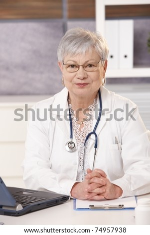 Portrait of medical expert at work, looking at camera, smiling.? - stock photo