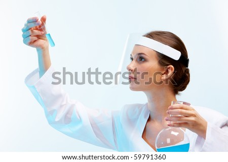 Portrait of medical specialist looking at flask on a white background - stock photo