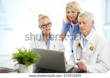 Portrait of medical staff sitting at hospital. Doctors and nurse sitting in front of computer and consulting. - stock photo