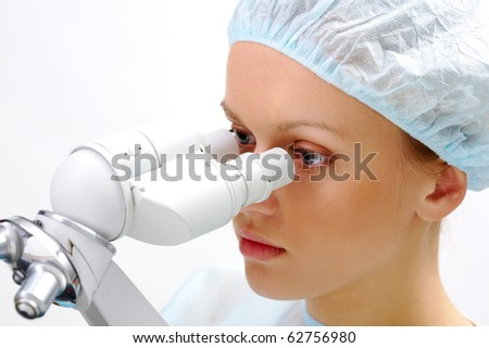 Portrait of medical student looking through microscope in laboratory - stock photo