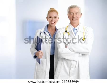 Portrait of medical team standing at hospital. Senior professor with arms crossed and female doctor holding clipboard in her hand while looking at camera and smiling.  - stock photo