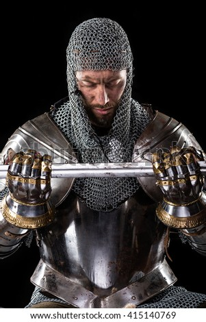 Portrait of Medieval Dirty Face Warrior with chain mail armour and Sword in hands. Black Background - stock photo