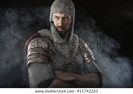 Portrait of Medieval Dirty Face Warrior with chain mail armour. Smoke Cloud on Dark Background - stock photo