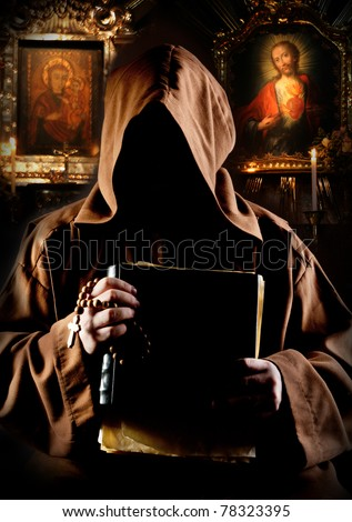 Portrait of medieval monk with bible in church - stock photo